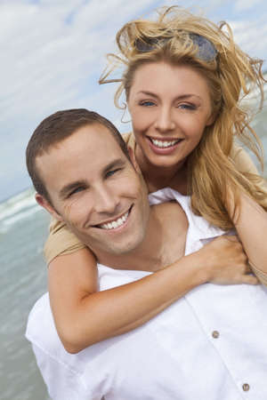 toothy: A young man and woman embracing as a romantic couple laughing and having fun on a beach