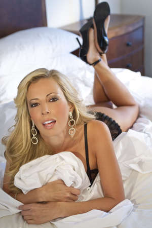 high heeled: A beautiful and sexy young blond woman on her bed wearing black lingerie and high heeled shoes Stock Photo