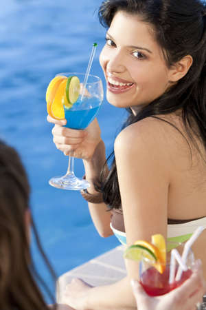 Stunningly beautiful young latina Hispanic woman laughing and  drinking a cocktail by a blue swimming pool with her friend in the foreground. photo
