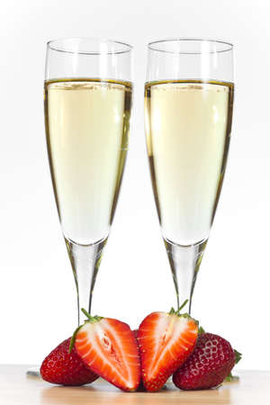 champagne flute: Two flute glasses of champagne with sliced strawberries. Stock Photo