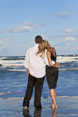 lovers holding hands: A young man and woman romantic couple in love arms around each other cuddling on a beach with a bright blue sky