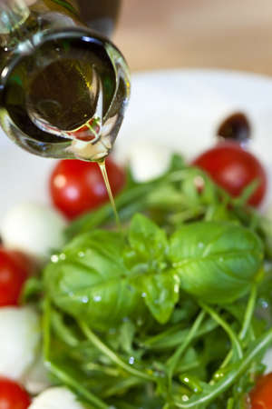 salad dressing: Close up macro photograph of olive oil dressing being poured onto a fresh rocket and basil salad with cherry tomatoes and balsamic vinegar Stock Photo