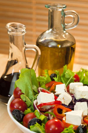 balsamic vinegar: Fresh lettuce, tomato, red pepper, red onion, black olive and feta cheese salad with bottles of olive oil and balsamic vinegar dressing in the background.