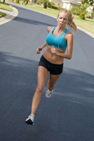portable mp3 player: A beautiful fit and healthy blond woman road running while listening to music on her portable mp3 player