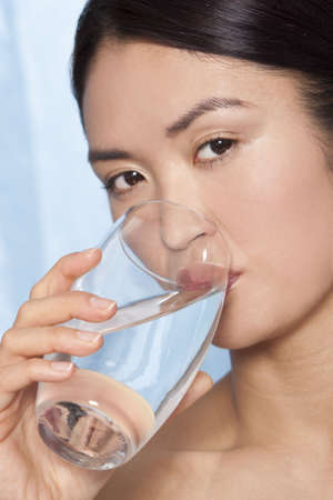 A beautiful Japanese Asian woman drinking a glass of pure clear mineral water