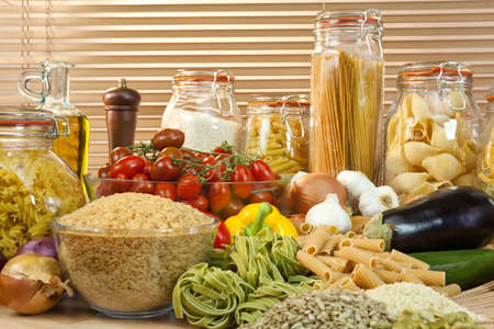 pulses: A display of healthy foods including various vegetables, jars of pasta, rice, seeds, onions, garlic, olive oil, aubergine, tomatoes, peppers, spaghetti and courgettes