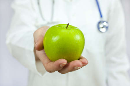 Healthy eating or lifestyle concept shot of a doctor holding and offering a green apple Standard-Bild
