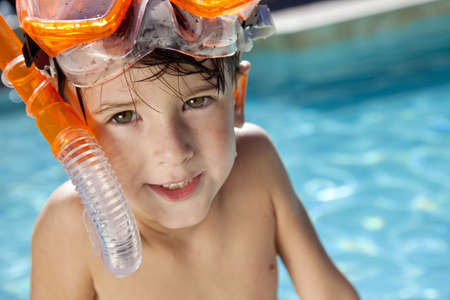 A happy young boy relaxing on the side of a swimming pool wearing orange goggles and snorkel