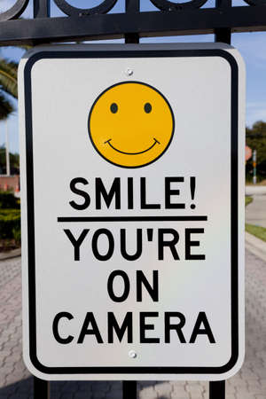 affixed: A Smile Youre on Camera sign affixed to security gates Stock Photo