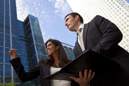 asian executive: A smiling Indian Asian businesswoman and her male colleague taking part in a happy business meeting outside in a modern city environment