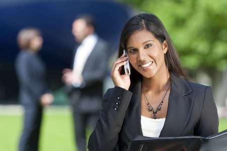 A beautiful young Asian businesswoman with a wonderful smile chatting on her cell phone with her colleagues out of focus behind her.