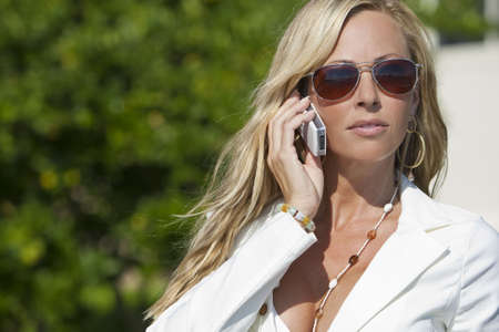 A beautiful young blond woman wearing aviator sunglasses and a white suit talking on her cell phone in a sunny location Stock fotó