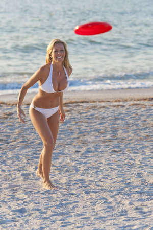 A beautiful young blond woman in a white bikini playing at the beach photo