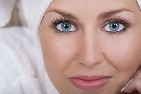 toweling: Close up studio portrait of a beautiful blond haired blue eyed female model wearing a white toweling robe with her her wrapped in a white towel Stock Photo