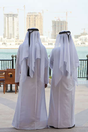 Two anonymous Arab men in traditional white clothing of dish dash and shemagh looking at the construction of new modern skyscrapers on the horizon Standard-Bild