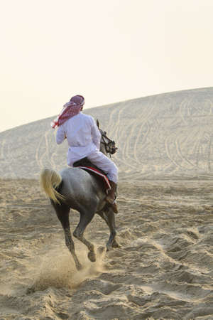 An anonymous Arab man in traditional clothing riding his horse in the sand of a desert bathed in golden sunlight