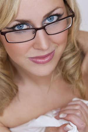 美しいセクシーな若い女性 smling、メガネを着用し、白いシートに包まれました。