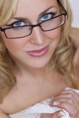 A beautiful sexy young woman smling, wearing glasses and wrapped in a white sheet photo