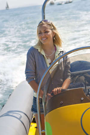 A stunningly beautiful young woman driving a speedboat and having fun. photo
