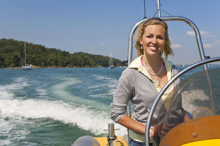 wealthy lifestyle: A stunningly beautiful young woman driving a speedboat and having fun with the Mediterranean coast and yachts in the background Stock Photo