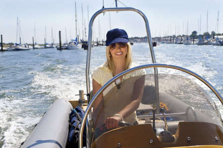 A stunningly beautiful young woman having fun driving a speedboat with moored sailing boats in the background