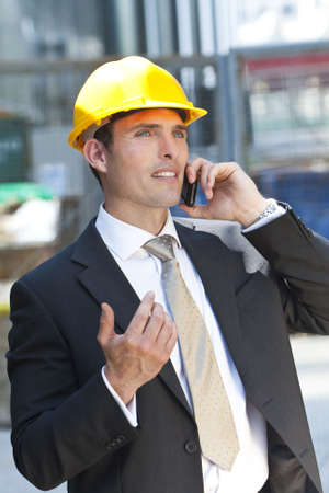 A man in a yellow hard hat and suit on an industrial or constructin site talking on his cell phone photo