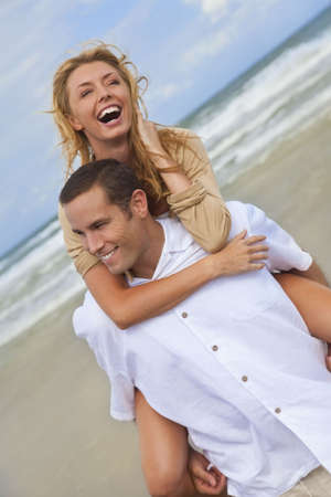 A young man and woman having fun as a romantic couple on a beach with the man carrying the woman on his back piggy back style. photo