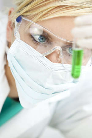A blond medical or scientific researcher or doctor looking at a test tube of green liquid in a laboratory while wearing surgical mask and safety glasses. photo