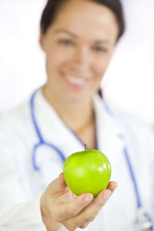 Healthy eating or lifestyle concept shot of a smiling woman doctor holding and offering a green apple, the focus is on the apple in the foreground. photo