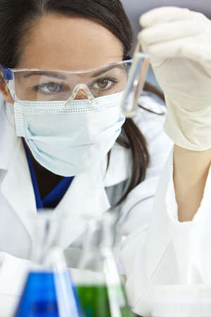 surgical mask woman: A female medical or scientific researcher or doctor looking at a liquid clear solution in a laboratory. Stock Photo
