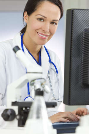 A smiling female medical or scientific researcher or woman doctor using a computer in a laboratory with microscope and other equipment in the foreground. Stock Photo - 6875904