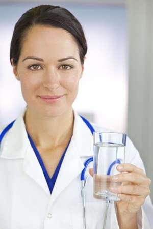 Disparo saludable, comer o estilo de vida, en el concepto de una mujer femenina sonriente doctor explotaci�n y un vaso de agua clara
