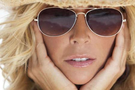 Asombrosamente bella y sexy rubia joven en el sombrero de vaquero de paja y las gafas de sol