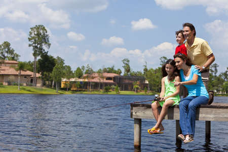 A modern family of mother, father, children, son and daughter fishing in a lake off a jetty on a sunny day photo