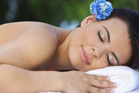A beautiful brunette hispanic latina woman relaxing outside on a massage table at a health spa with a blue flower in her hair Stock Photo - 7017778