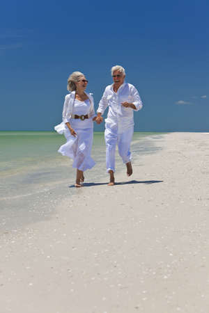 happy retirement: Happy senior man and woman couple running, laughing and holding hands on a deserted tropical beach with bright clear blue sky