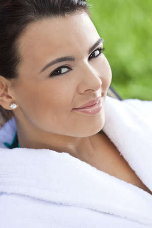 Portrait of a beautiful young Latina Hispanic woman smiling in a white bathrobe outside at a health spa Stock Photo - 7055140
