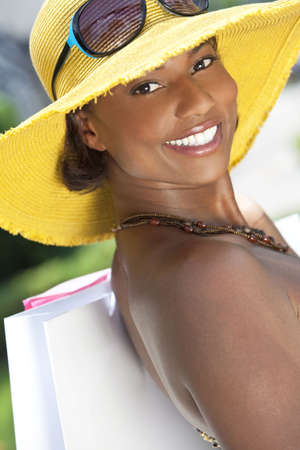 Beautiful and Fashionable African American woman smiling with colorful hat and shopping bags photo
