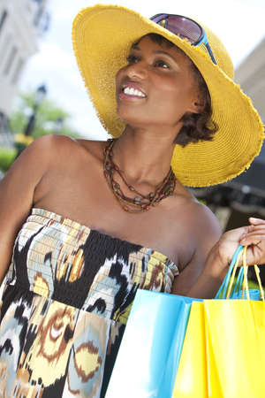 Beautiful and Fashionable African American woman with colorful shopping bags photo