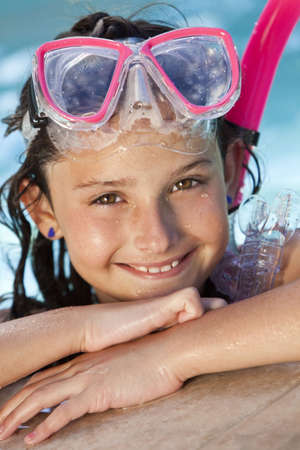 A cute happy young girl child relaxing on the side of a swimming pool wearing pink goggles and snorkel photo