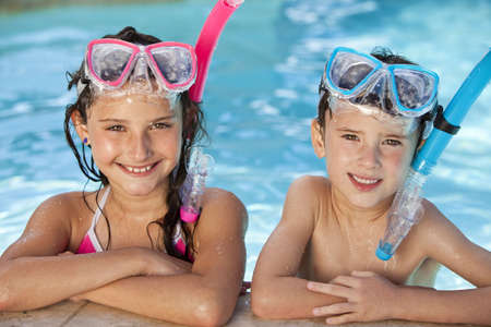 swim goggles: Felices los ni�os, el ni�o y la ni�a, relajante al lado de una piscina que llevaba gafas azules y rosas y snorkel Foto de archivo