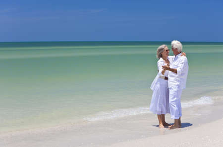 retirement couple: Happy senior man and woman couple dancing and holding hands on a deserted tropical beach with bright clear blue sky