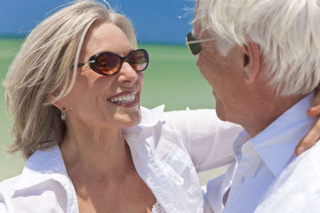 Happy senior man and woman couple dancing and holding hands on a deserted tropical beach with bright clear blue sky photo