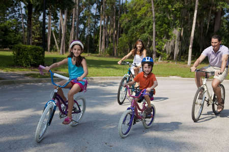 A modern family of two parents and two children, a boy and a girl, cycling together. Stock Photo - 7112323