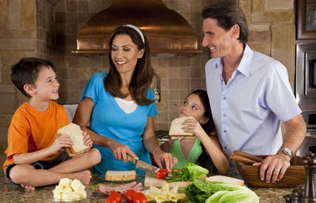 An attractive happy, smiling family of mother, father, son and daughter making healthy sandwiches with ham, cheese and fresh salad in a modern kitchen