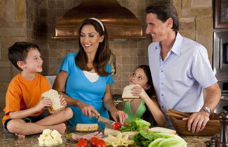 Una familia feliz y sonriente atractiva de madre, padre, hijo y su hija haciendo s�ndwiches saludables con jam�n, queso y ensalada fresca en una cocina moderna Foto de archivo