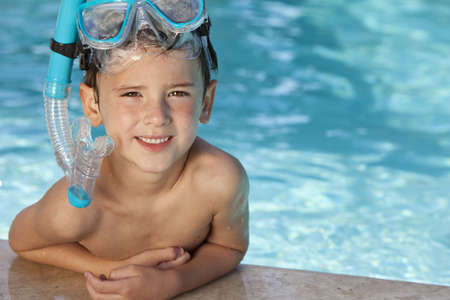 A happy young boy relaxing on the side of a swimming pool wearing blue goggles and snorkel Stock Photo