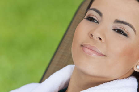 Portrait of a beautiful young Latina Hispanic woman smiling in a white bathrobe outside at a health spa Stock Photo - 7127231