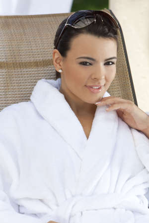Portrait of a beautiful young Latina Hispanic woman smiling in a white bathrobe outside at a health spa Stock Photo - 7127235