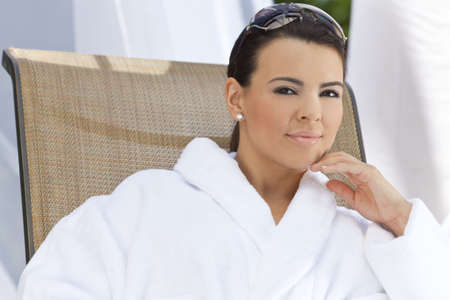 Portrait of a beautiful young Latina Hispanic woman smiling in a white bathrobe outside at a health spa Stock Photo - 7127232